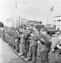 Le 13 août 1961, la construction du mur de Berlin est complétée. Cette photo montre des hommes des « groupes de combat de la classe ouvrière » (Kampfgruppen der Arbeiterklasse), organisation paramilitaire est–allemande, sur le côté ouest de la Porte de Brandebourg qui se tiennent exactement sur la ligne de démarcation.